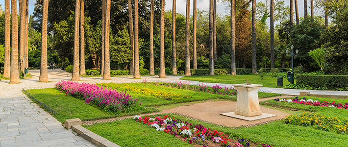 flowers and fountains in the centre with trees and stoned pathways surrounding the outside part of the image