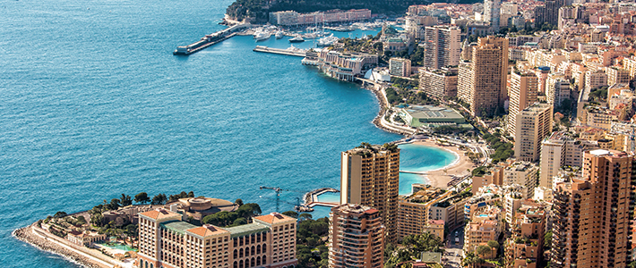 ariel shot of monte carlo with blue ocean to the left of the image and buildings to the right